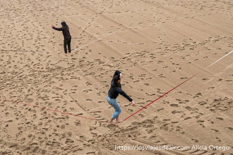una chica y un chico haciendo equilibrios en cuerdas tensas encima de arena de playa en biarritz