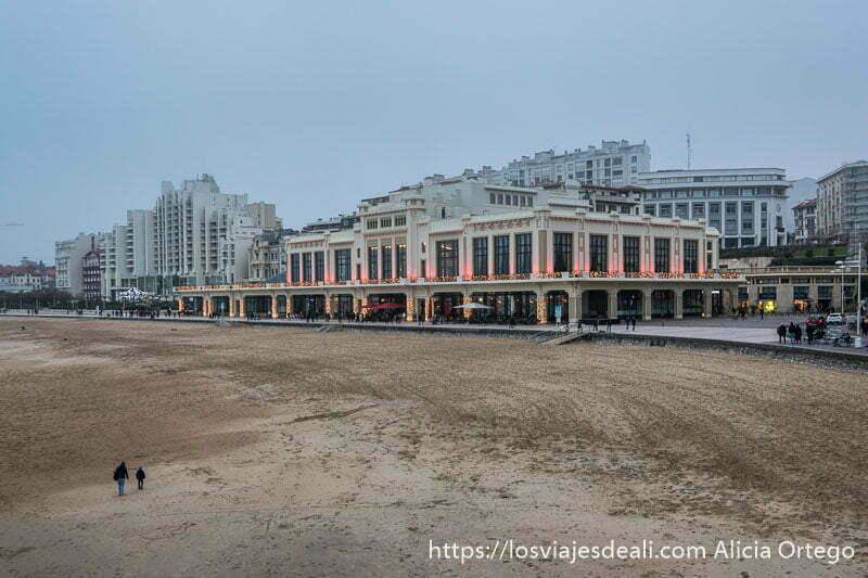 casino de biarritz con luces rojas y la playa delante con dos figuras andando por la arena