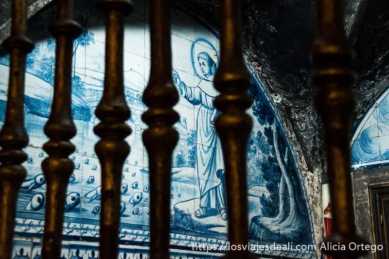 azulejos con imagen de un santo mirando un río y los peces asomando la cabeza hacia él, detrás de unas rejas en el centro de lisboa