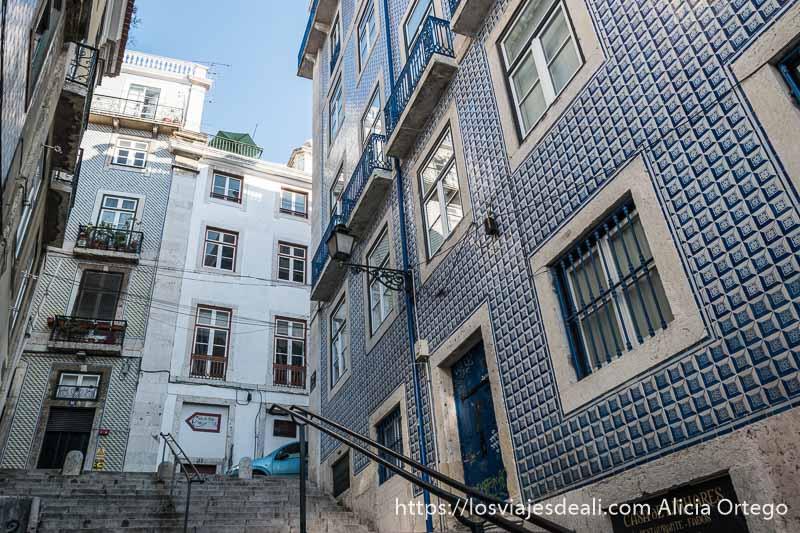 calle con escaleras y barandillas de hierro en el centro alrededor edificios llenos de azulejos en tonos azules en el centro de lisboa