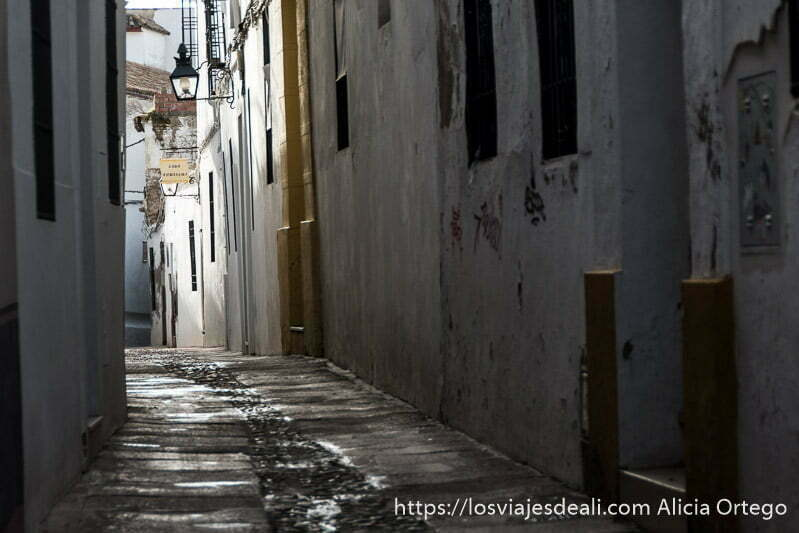 callejón de la judería con farola y casas pintadas de blanco y amarillo en el centro histórico de córdoba