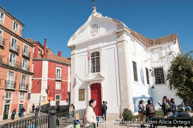 iglesia de santa lucía pintada de blanco con tejado de tejas y puerta roja y un mural de azulejos en el lateral en el centro de lisboa