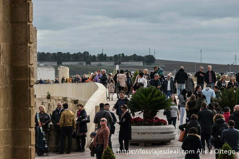 puente romano de córdoba lleno de gente que viene y va