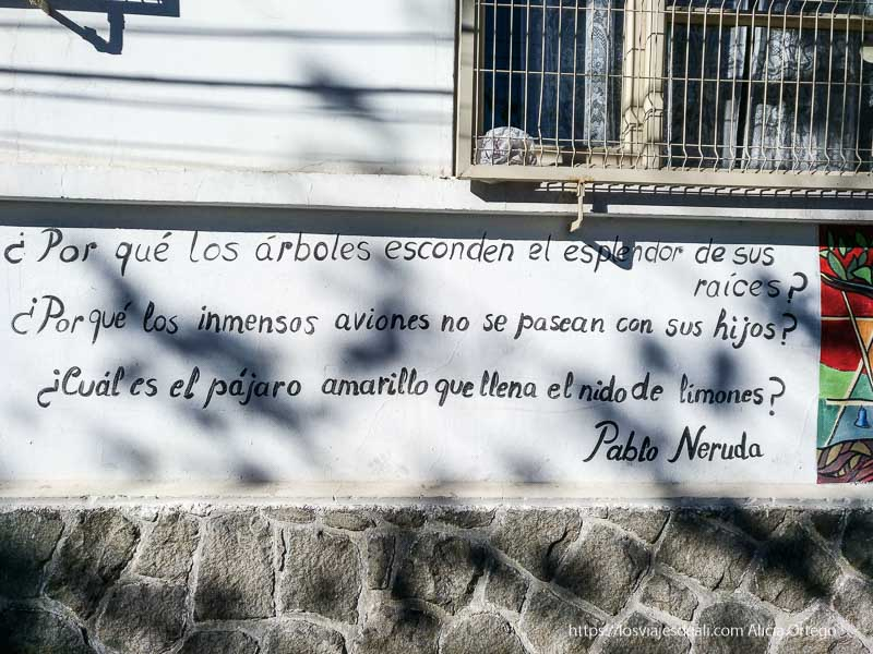 """poema de Pablo Neruda pintado en una pared que dice """"Por qué los árboles esconden el esplendor de sus raíces? ¿por qué los inmensos aviones no se pasean con sus hijos? ¿cuál es el pájaro amarillo que llena el nido de limones?"""
