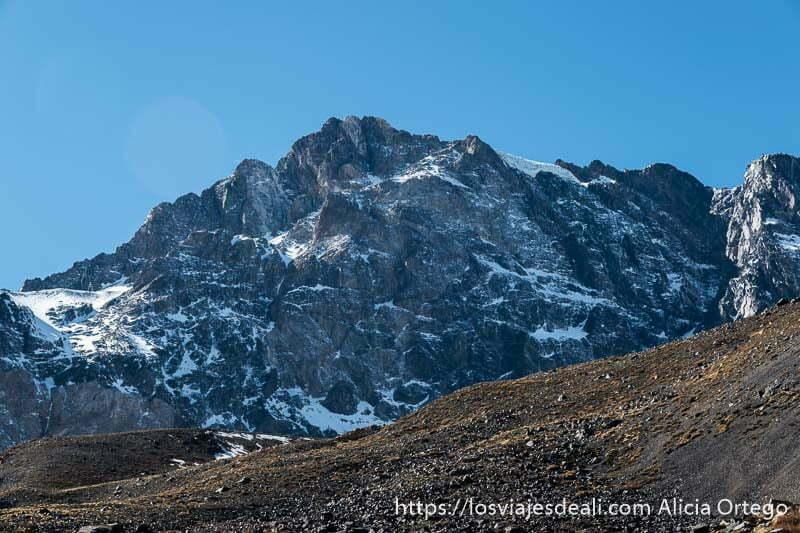 montaña de roca negra salpicada de nieve en la escapada al cajón del maipo