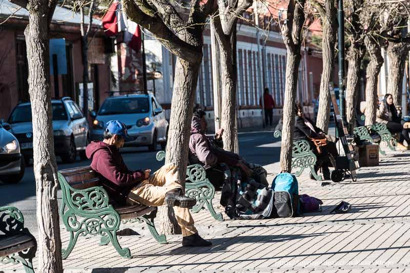 fila de bancos de hierro y madera con árboles intercalados y personas sentadas al sol en la escapada al cajón del maipo