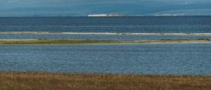 lago khovsgol desde la orilla con isla al fondo y montañas con bosques al otro lado