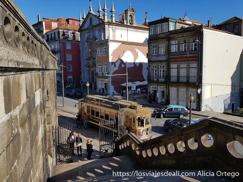 escalera de piedra con tranvía de madera abajo y una iglesia al fondo con mural urbano en el costado
