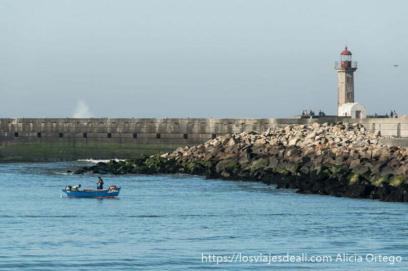 a la derecha faro de filgueiras con linterna roja y el espigón de bloques de cemento y a la izquierda una barca de pescadores