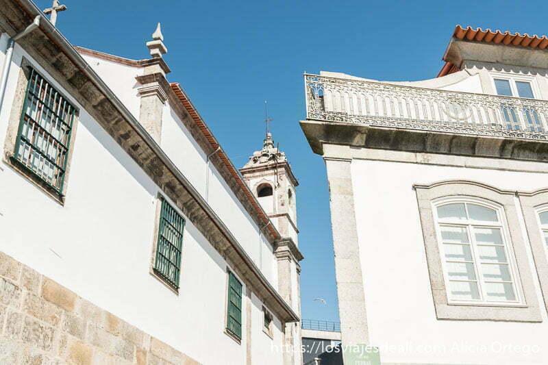 muros blancos de iglesia y una casa con elementos de piedra alrededor de ventanas y esquinas