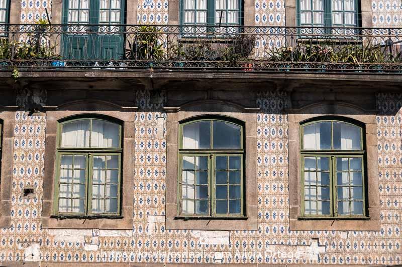 fachada de azulejos con tres ventanas y un balcón con algunas plantas sobre ellas en oporto