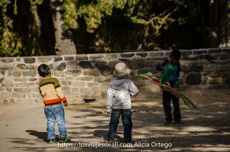 tres niños peruanos de 3 o 4 años jugando con una cometa de colores