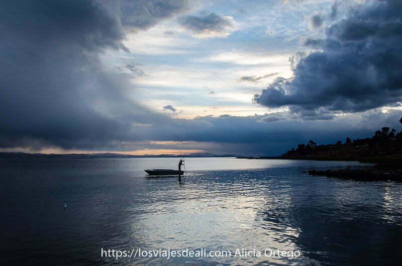 barquero empujando con pértiga su barca en el lago titicaca uno de los lugares maravillosos de perú