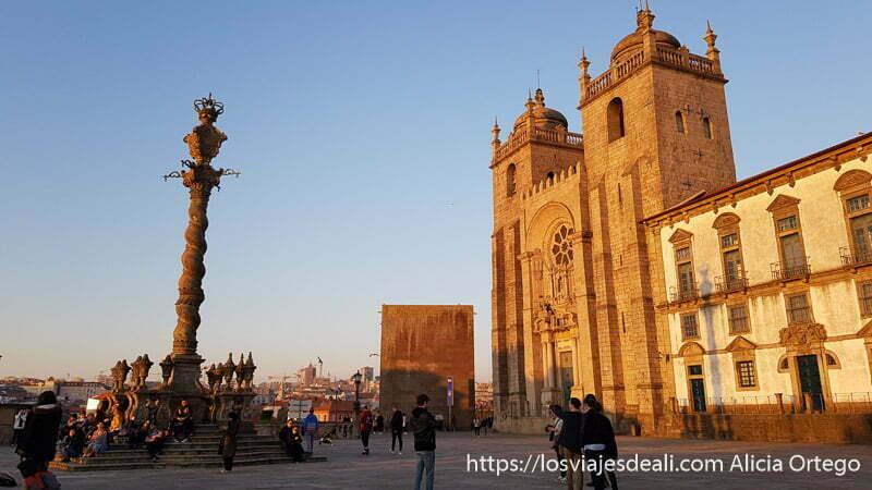 plaza de la catedral con dos torres y un cruceiro enfrente todo con luz de atardecer en oporto