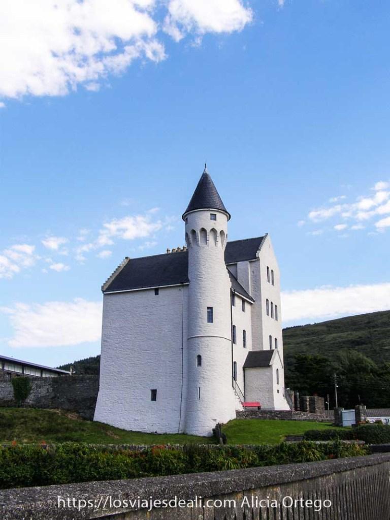 casa castillo con una torre circular y tejado en punta pintado de blanco en caherciveen en el ring of kerry