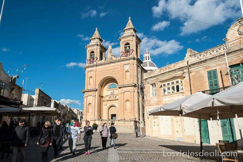 iglesia de piedra rojiza con dos campanarios y plaza donde camina la gente