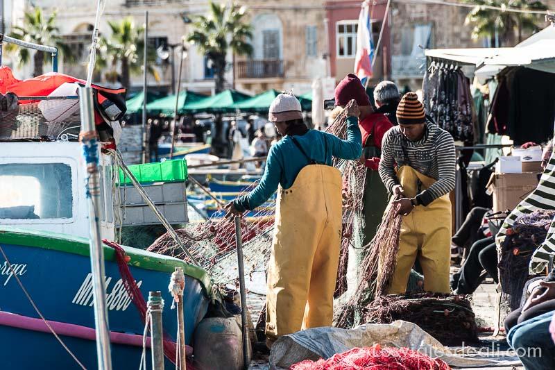 pescadores migrantes desenredando redes en el puerto