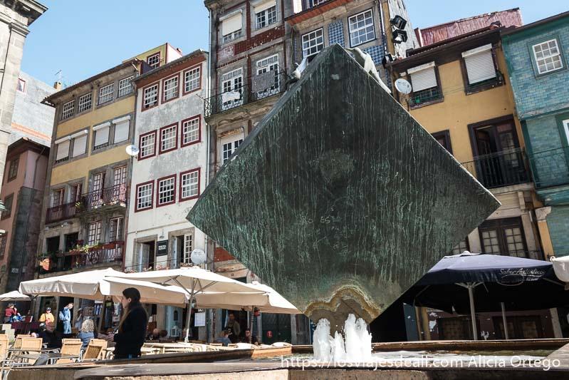 escultura de hierro con forma de cubo y fuente en la base contrastando con casas de colores de la ribeira lugares que ver en oporto