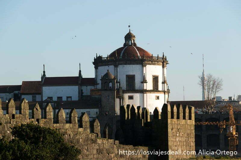 edificio circular del monasterio da serra do pilar y murallas de Oporto en primer plano al atardecer uno de los lugares que ver en Oporto