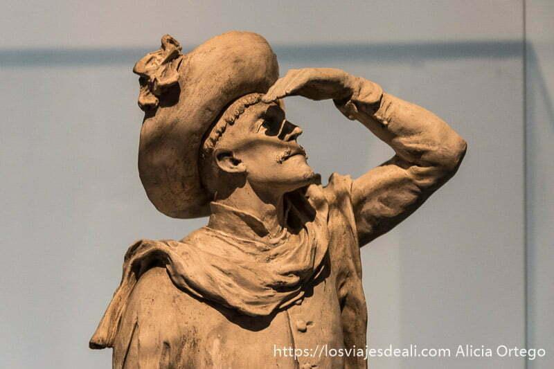 estatua de Enrique el Navegante mirando hacia arriba mientras se protege del sol con la mano
