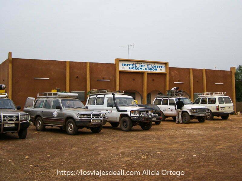 fachada del hotel de l'amitie de gorom gorom con 5 coches 4x4 aparcados delante
