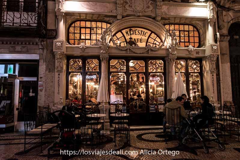 fachada del café majestic de estilo art nouveau iluminada por la noche con terraza delante