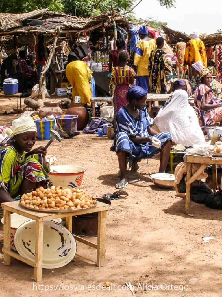 mujeres sentadas en banquetas bajitas vendiendo patatas en el mercado africano de gorom gorom