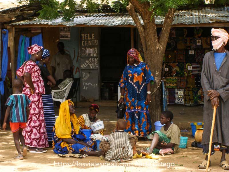 mujeres peul y hombre con turbante y bastón a la sombra en una calle de gorom gorom