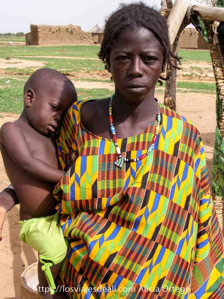 chica joven bella con vestido de colorines y collar de piedras de colores y su bebé apoyado en la cadera