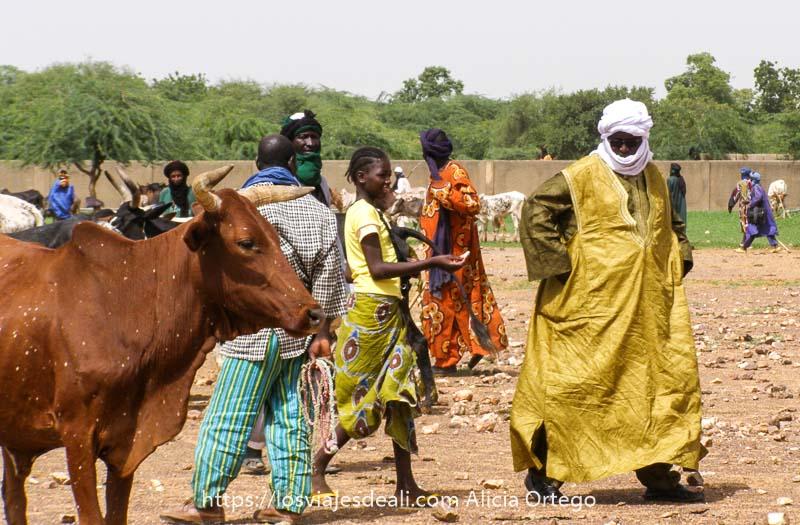 tuareg con vestido de color amarillo y turbante blanco seguido por una niña con pelo de trenzas en el mercado africano de gorom gorom