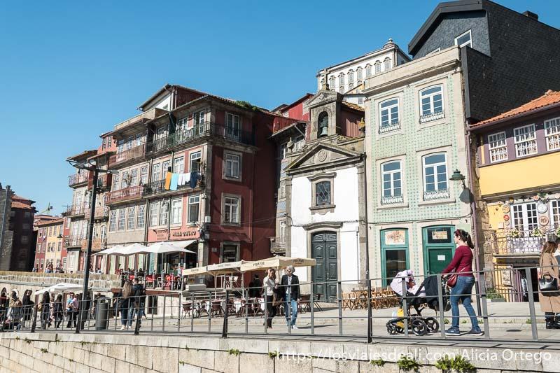 guia de oporto: calle de la ribeira con gente paseando al sol y una ermita entre casas de azulejos