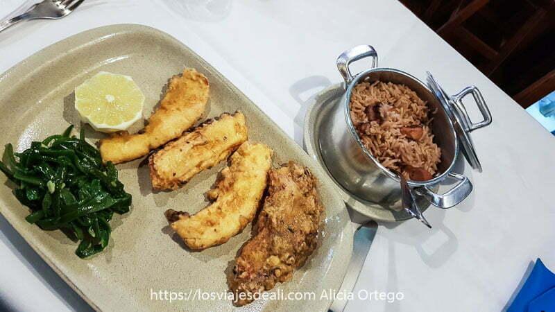 plato de filetes de pulpo rebozados y cacerola pequeña con arroz con salchichas
