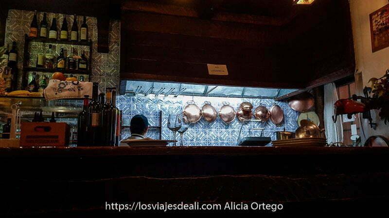 restaurante a grade con cocina de azulejos y perolas de cobre colgadas en la pared
