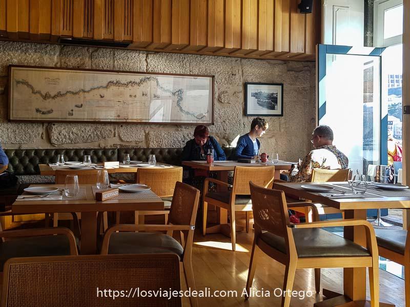 comedor del restaurante Muro Bacalhoeiros con gran mapa en pared de piedra