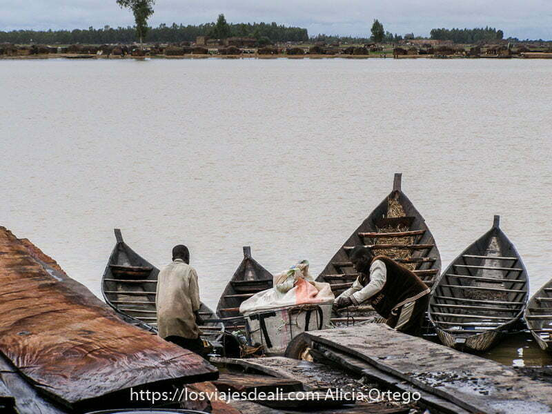 Fotos de Mali: río níger con agua marrón y en primer plano 4 barcas colocadas en abanico y dos hombres cargando cosas