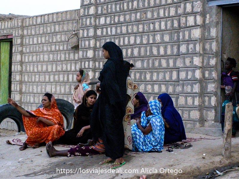 mujeres tuareg sentadas en el suelo a la puerta de su casa con vestidos de colores en Tombuctu