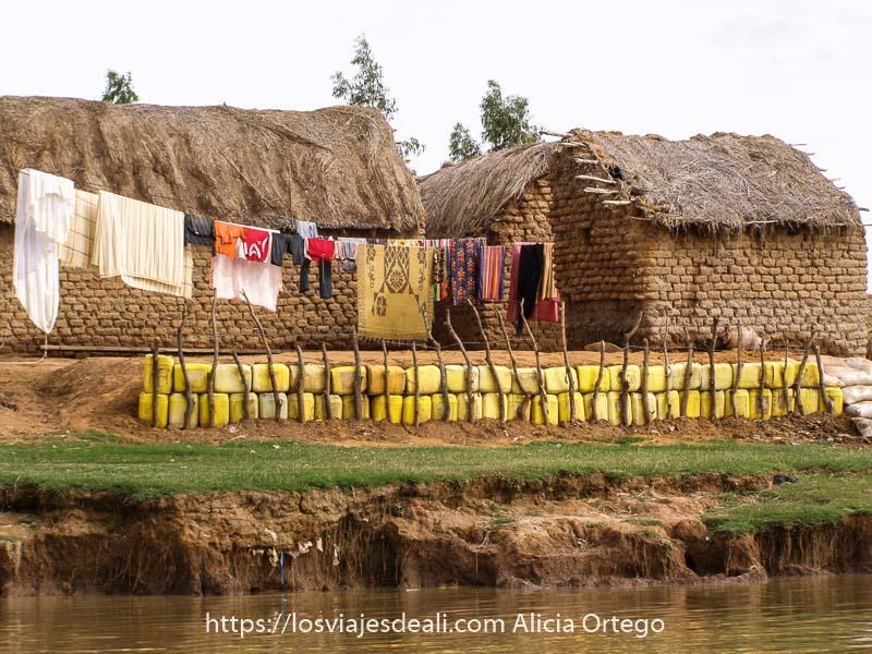 casas de ladrillos de adobe junto a la orilla del Níger con hilera de ropa tendida y dique hecho con bidones de plástico amarillo