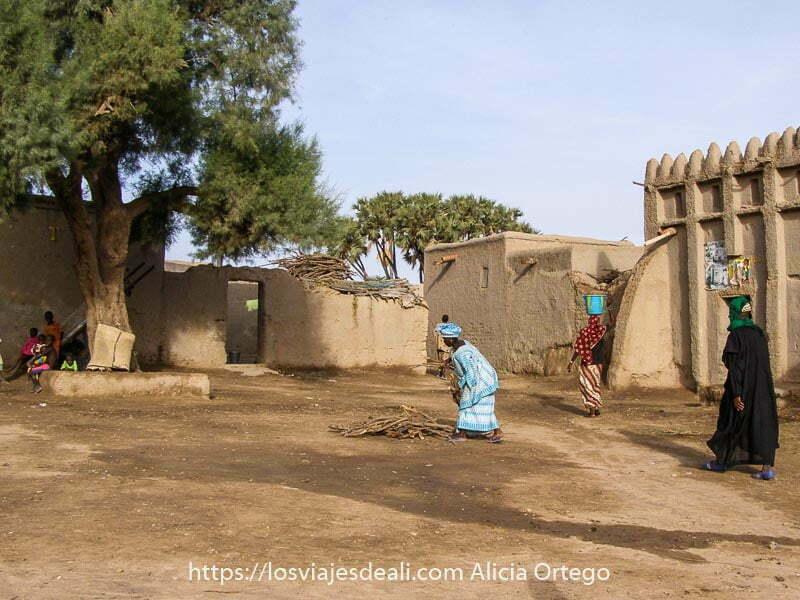 plaza con gran árbol y edificios de adobe alrededor y una mujer en el centro vestida de azul agachándose para recoger leña