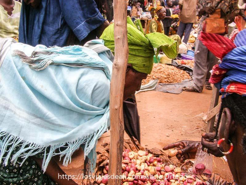 mujer africana con pañuelo verde en la cabeza y chal azul se agacha en un puesto de nueces de karité para comprar