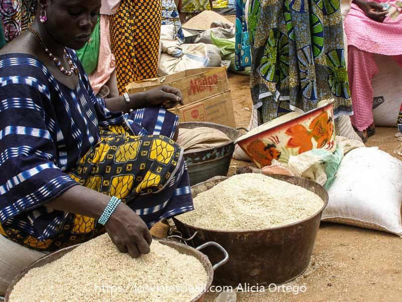 Fotos de Maii: mujer sentada en el suelo con barreños de arroz a su alrededor en el mercado de Djenne