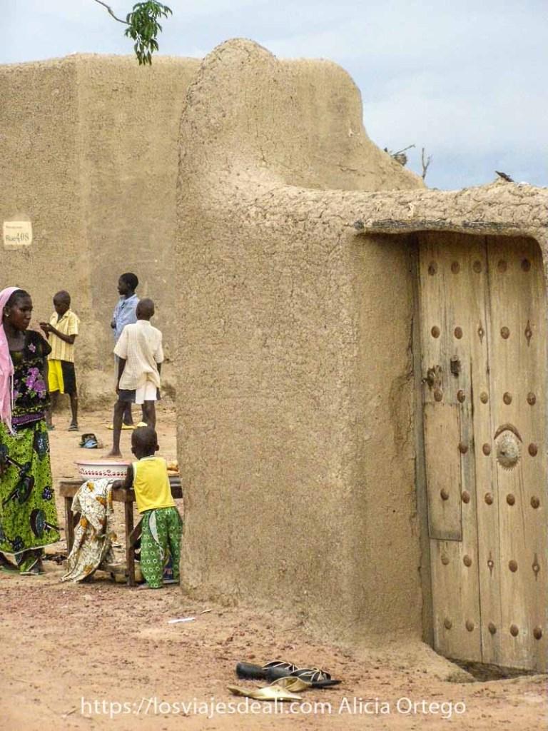 edificio de adobe con puerta de madera y remaches metálicos y a la izquierda una mujer y unos niños en Djenne