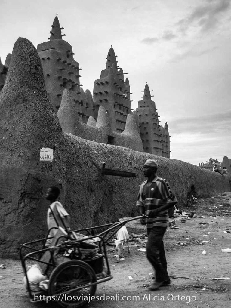 Fotos de Mali: hombre empujando un carrito con cosas y un niño andando al lado delante de la gran mezquita de barro de djenne