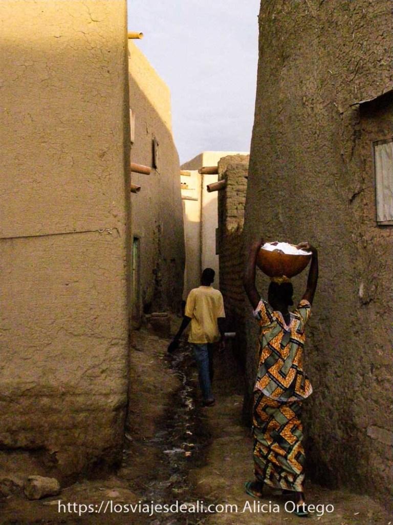 chica joven entrando en callejón estrecho de djenne con calabaza en la cabeza llena de algo blanco y casas de barro alrededor