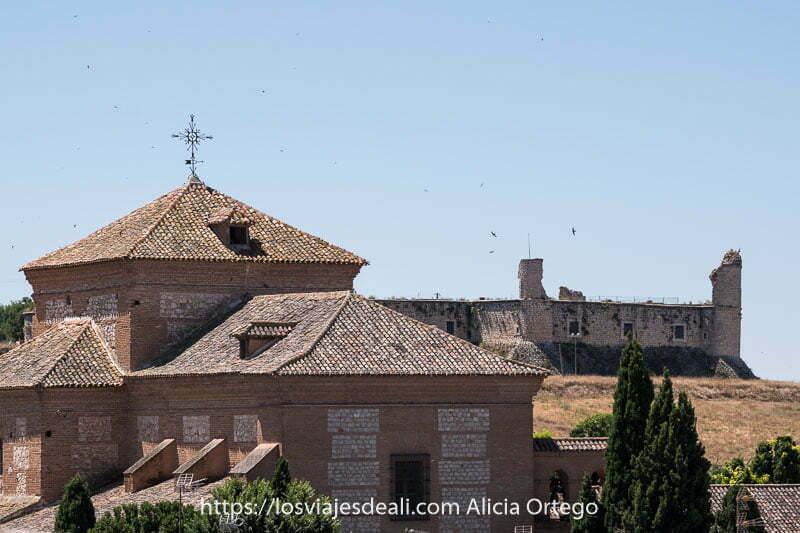 uno de los castillos con pájaros sobrevolando y el edificio de un convento delante