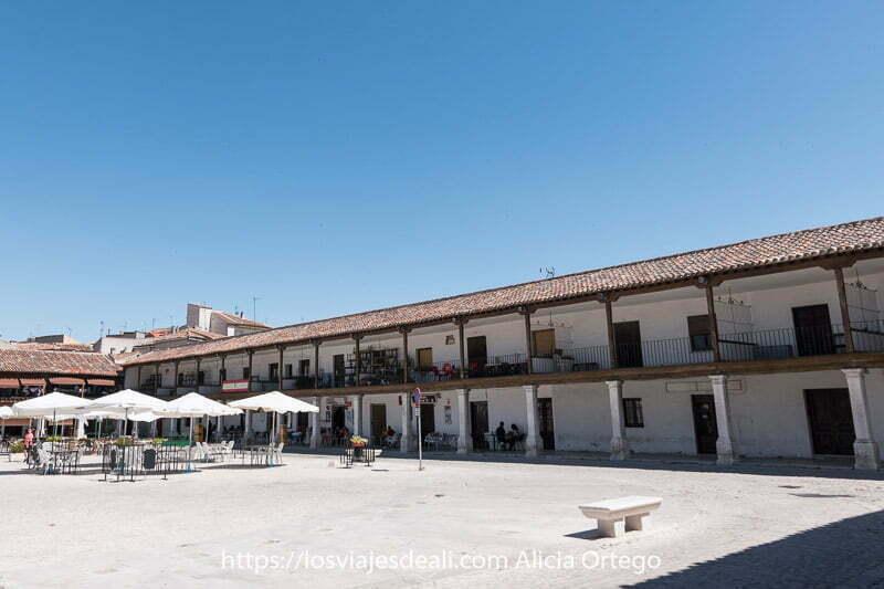 plaza de colmenar de oreja con una terraza con sombrillas y rodeada de soportales con columnas y edificios de dos plantas