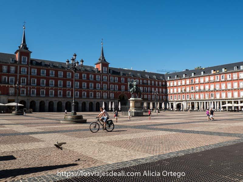 plaza mayor en el centro de Madrid con ciclista atravesándola y una paloma posándose en el suelo