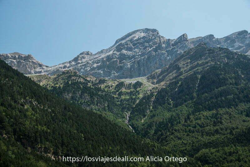 picos de roca con laderas de bosque y una cascada en el centro