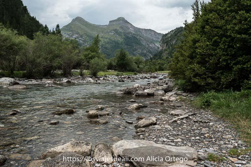 río Ara con poco caudal y lecho de rocas entre praderas y montañas al fondo