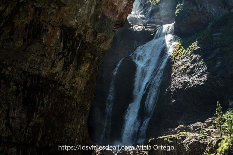 Cascada de Ordesa entre rocas con un rayo de sol entrando e iluminando una parte