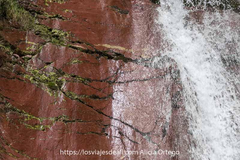 roca de color rojo con vetas de musgo y cascada fluyendo sobre ella en el Valle de Pineta